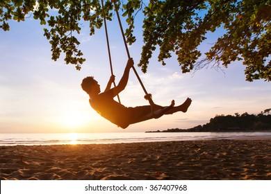 swing on paradise tropical beach at sunset, happy people enjoying summer