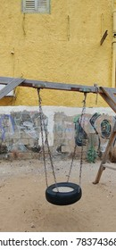Swing from a round tire near a house with graffiti
