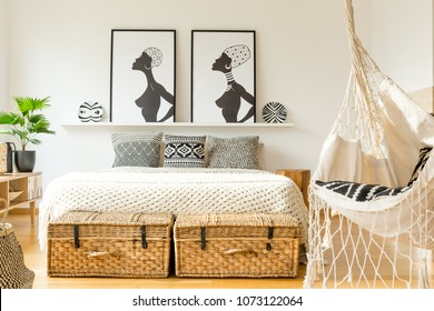 Swing in a rustic bedroom interior with king size bed, graphics, plant and straw baskets