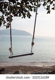 Swing with the sea on background on summer relax time
