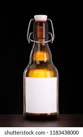 Swing top bottle with blank label isolated on black background