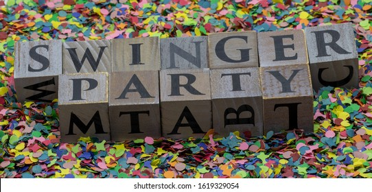 Swinger written on wooden blocks isolated on confetti background