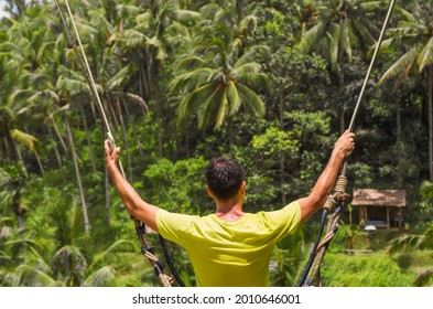 Swinging above the jungle with palm trees in Ubud, Bali, Indonesia. Happy leisure time for a male traveler.
