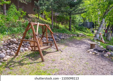 Swinging bench chair swing seat outside outdoors relax wood cabin up north lake path rocks