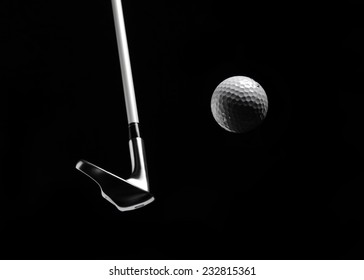 Swinging a golf iron/club with a golf ball in a mid air position, isolated on black with copy space.