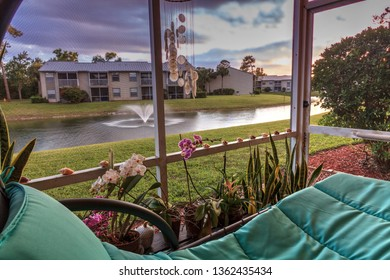 Swinging lounge chair on a lanai at sunset as it overlooks a pond with a fountain with golden light filtering into the patio.