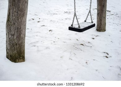 Swings filled with fresh snow on a deserted playground, on a cloudy spring day.