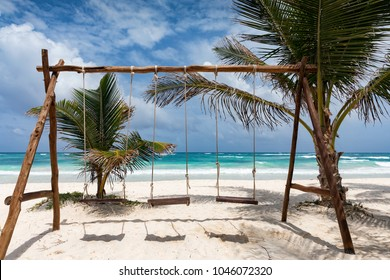 Swings on a tropical beach with turquoise water and blue sky in Tulum, Mexico