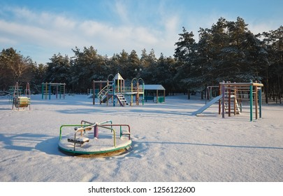 Swings at the playground covered with snow in winter time. Trees covered with hoarfrost.