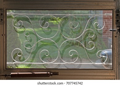 Swirly decorative grate throwing a shadow onto a screened window in a door with grass and a patio behind it