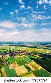 Swirzerland. Little towns and villages with green fields during the sunny day. Forest at the background. Cloudy sky