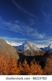 Swiss Alps in the fall, with larch trees turning golden, and snow on the summits.  Perfect weather for hiking