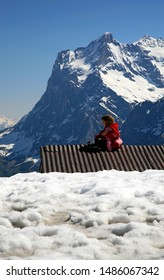 Swiss Alps Switzerland May 2016. Young girl in red coat sitting on rusty corrugated roof of building buried under the snow. Snow in front and North face of the Eiger in rear. Blue sky.
