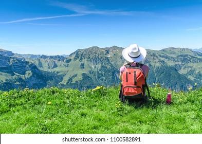 Swiss Alps. A woman in a white hat sitting on a green meadow, drinking water from a bottle and admiring the mountain scenery. Engelberg Resort
