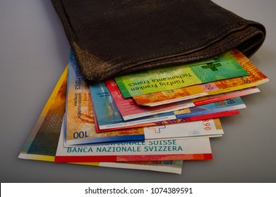 Swiss cash paper bills are in the old wallet. The purse with Switzerland francs lies on a light background.