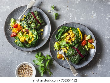 Swiss chard packets. Chard leaves stuffed with turmeric lentils and vegetables. Vegetarian healthy food concept. On a grey background, top view