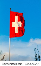 Swiss Confederation, Switzerland national flag waving on blue sky background