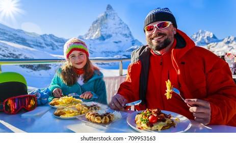 Swiss dinner - family skiers enjoying break for lunch, mountain view Matterhorn, Switzerland.