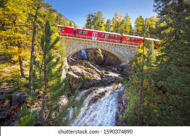Swiss electric trains pass mountain alpine gorges over beautiful stone bridges over stormy clean rivers and waterfalls, among a golden autumn forest.