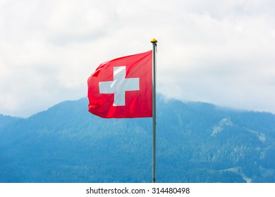 Swiss flag against Alps mountains. Horizontal shot