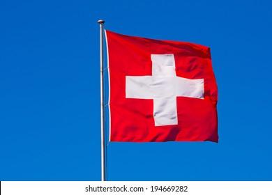 Swiss flag against blue sky