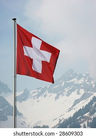 Swiss flag against snowy Alps