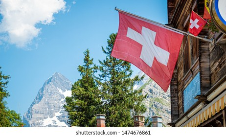 Swiss flag attached to a wooden hut in Switzerland - THE SWISS ALPS, SWITZERLAND - JULY 22, 2019