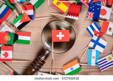 Swiss flag. Economic growth, Imports and Exports, Armaments and Security concept. Magnifying glass and flags of different countries
