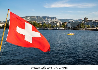 A swiss flag floating in the wind over the Lake Geneva, with the city of Geneva in the background.