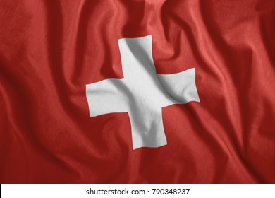 The Swiss flag flutters in the wind. Colorful, national flag of Switzerland. Patriotism.