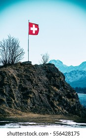 Swiss flag flying above a mountain in the alps covered in light winter snow on a cold sunny blue sky day