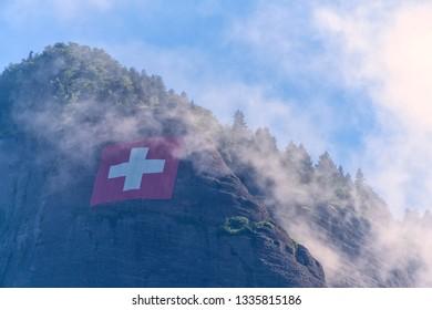 Swiss flag high on mountain top through the fog