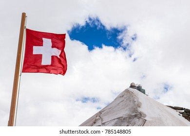 Swiss flag on Jungfraujoch with Sphinx observartory in the background. Jungfraujoch, Bernese Oberland, Switzerland