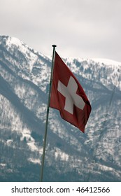 swiss flag with snow capped mountains in the background