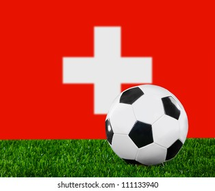 The Swiss flag and soccer ball on the green grass