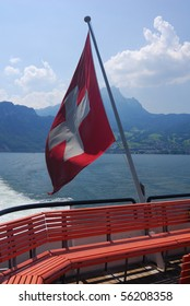 A Swiss flag at the stern of a boat on a Swiss lake.