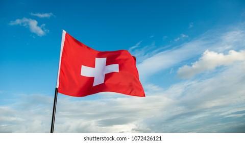 Swiss flag waving against sky