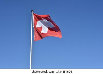 Bandera suiza ondeando en el cielo azul