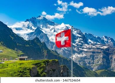 Swiss flag waving and tourists admire the peaks of Monch and Jungfrau mountains on a Mannlichen viewpoint, Bernese Oberland Switzerland