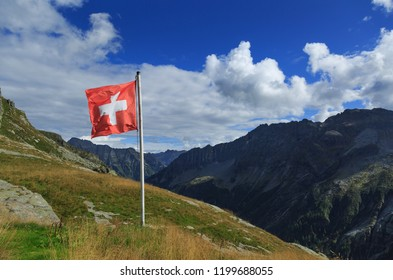 Swiss flag waving in the wind at a mountain hut in Ticino, Switzerland.