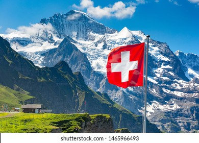 Swiss flag wavingon a Mannlichen viewpoint with peak of Jungfrau mountain on the background, Bernese Oberland Switzerland
