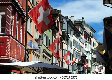 Swiss flags and colorful houses in a street in Zurich, Switzerland