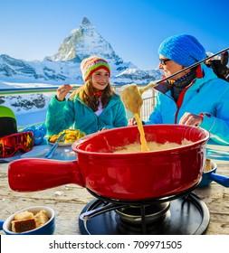 Swiss fondue cheese - skiers enjoying break for lunch, mountain view Matterhorn, Switzerland.
