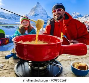 Swiss fondue dinner - family skiers enjoying break for lunch, mountain view Matterhorn, Switzerland.