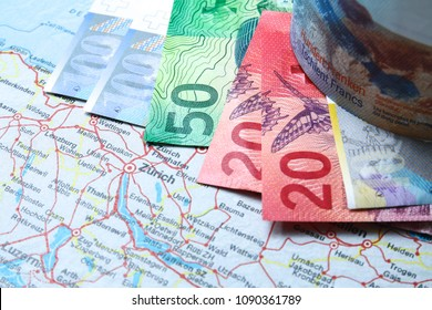 Swiss franc banknotes on map with Zurich city