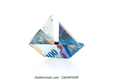 Swiss franc folded as boat over white background with reflection