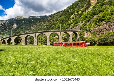Swiss mountain train Bernina Express under the viaduct, Switzerland