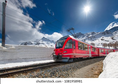 Swiss mountain train Bernina Express crossed Alps with snow wall.