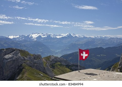 swiss mountains and flag on a roof