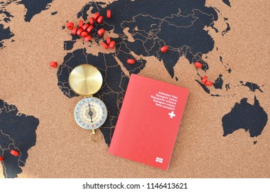 Swiss passport and compass on the pinboard map